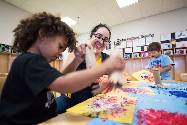 Stephanie Salazar, 502nd Force Support Squadron, child development program assistant, helps kids create a fire work painting, June 11, 2019, at the Gateway Child Development Center, Joint Base San Antonio-Lackland, Texas.