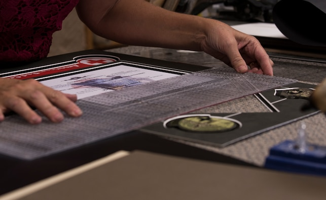 Tamra Windows, 90th Force Support Squadron Arts and Crafts Center employee, measures a framing mat before placing it into the custom built frame June 27, 2018, on F.E. Warren Air Force Base, Wyo. A few items that can be custom made in the shop are awards, shadow boxes and t-shirts. (U.S. Air Force photo by Senior Airman Abbigayle Williams)