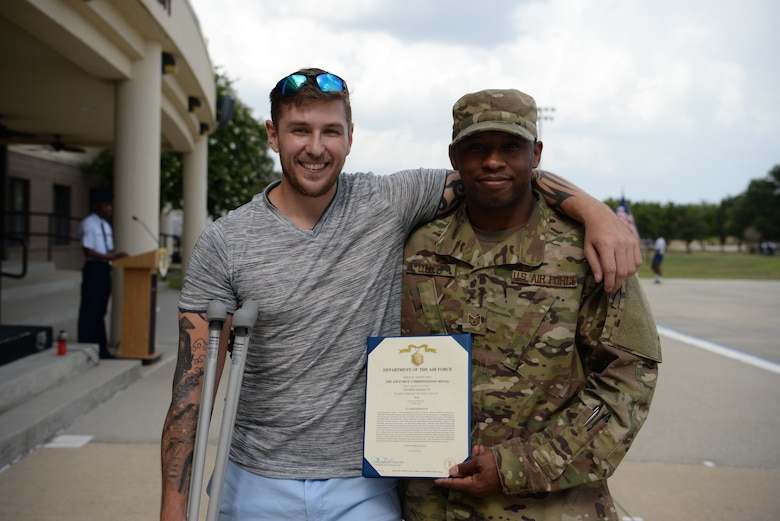 U.S. Air Force Tech. Sgt. Jonathan Collett, 336th Training Squadron cyber surety student, and Dennis Boney, Harrison County Police Department deputy, pose for a photo outside the Levitow Training Support Facillity on Keesler Air Force Base, Mississippi, June 27, 2019. Collett recieved an Air Force Commendation Medal for saving Boney after an accident that injured his leg. (U.S Air Force photo by Airman 1st Class Spencer Tobler)