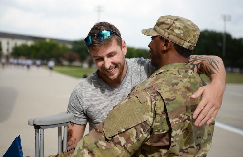 Dennis Boney, Harrison County Police Department deputy, hugs U.S. Air Force Tech. Sgt. Jonathan Collett, 336th Training Squadron cyber surety student, outside the Levitow Training Support Facillity on Keesler Air Force Base, Mississippi, June 27, 2019. A ceremony was held for Collett due to his heroic actions after rescuing Boney. (U.S Air Force photo by Airman 1st Class Spencer Tobler)