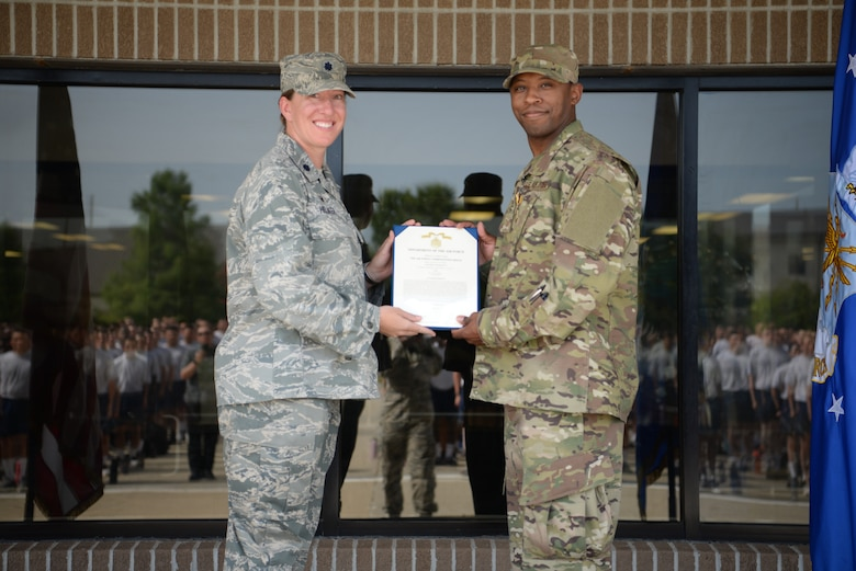 U.S. Air Force Lt. Col. Jill Heliker, 336th Training Squadron commader, and Tech. Sgt. Jonathan Collett, 336th Training Squadron cyber surety student, pose for a photo outside the Levitow Training Support Facillity on Keesler Air Force Base, Mississippi, June 27, 2019. Collett recieved an Air Force Commendation Medal for saving Dennis Boney, Harrison County Police Department deputy, after an accident that injured his leg. (U.S Air Force photo by Airman 1st Class Spencer Tobler)