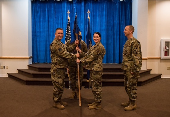 Colonel Robert Ewers, 90th Operations Group commander, passes the guidon to Lt. Col. Amy Grant, 321st Missile Squadron incoming commnader, during the 321st MS change of command ceremony June 28, 2019, on F.E. Warren Air Force Base, Wyo. The ceremony signified the transition of command from Lt. Col. Joel Douglas to Grant. (U.S. Air Force photo by Senior Airman Abbigayle Williams)