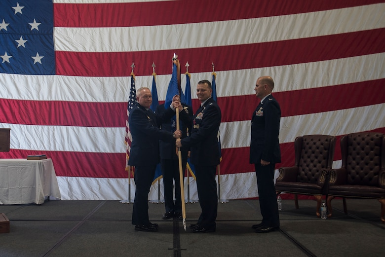Major Gen. Fred Stoss, 20th Air Force commander, passes the guidon to Col. Joshua Bowman, 582nd Helicopter Group outgoing commander, during the 582nd HG change of command ceremony June 28, 2019, on F.E. Warren Air Force Base, Wyo. The ceremony signified the transition of command from Bowman to Col. Jerry Crigger. (U.S. Air Force photo by Senior Airman Abbigayle Williams)