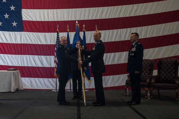 Major Gen. Fred Stoss, 20th Air Force commander, passes the guidon to Col. Jerry Crigger, 582nd Helicopter Group incoming commander, during the 582nd HG change of command ceremony June 28, 2019, on F.E. Warren Air Force Base, Wyo. The ceremony signified the transition of command from Col. Joshua Bowman to Crigger. (U.S. Air Force photo by Senior Airman Abbigayle Williams)