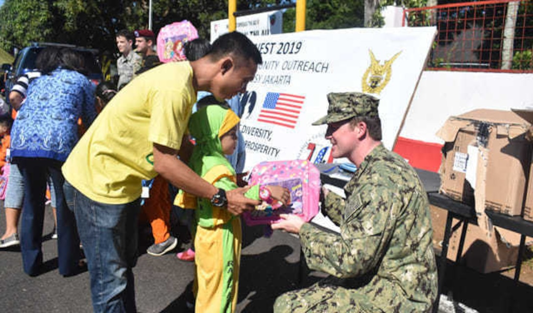 U.S. Navy Petty Officer 1st Class Nickolas Czyzewski, an analyst with the U.S. Indo-Pacific Command Augmentation Team-Indonesia, gives a backpack to a child during the Cope West 19 open house at Sam Ratulangi International Airport, Manado, Indonesia June 22, 2019.  During the event, a team of U.S. Embassy-Jakarta members set up a small kiosk showcasing U.S.-Indonesian 70th anniversary bilateral relations items and educational handouts for children. The team handed out educational books, back packs, writing supply materials, in commemoration of diplomatic relations between the U.S. and Government of Indonesia. (Courtesy photo)