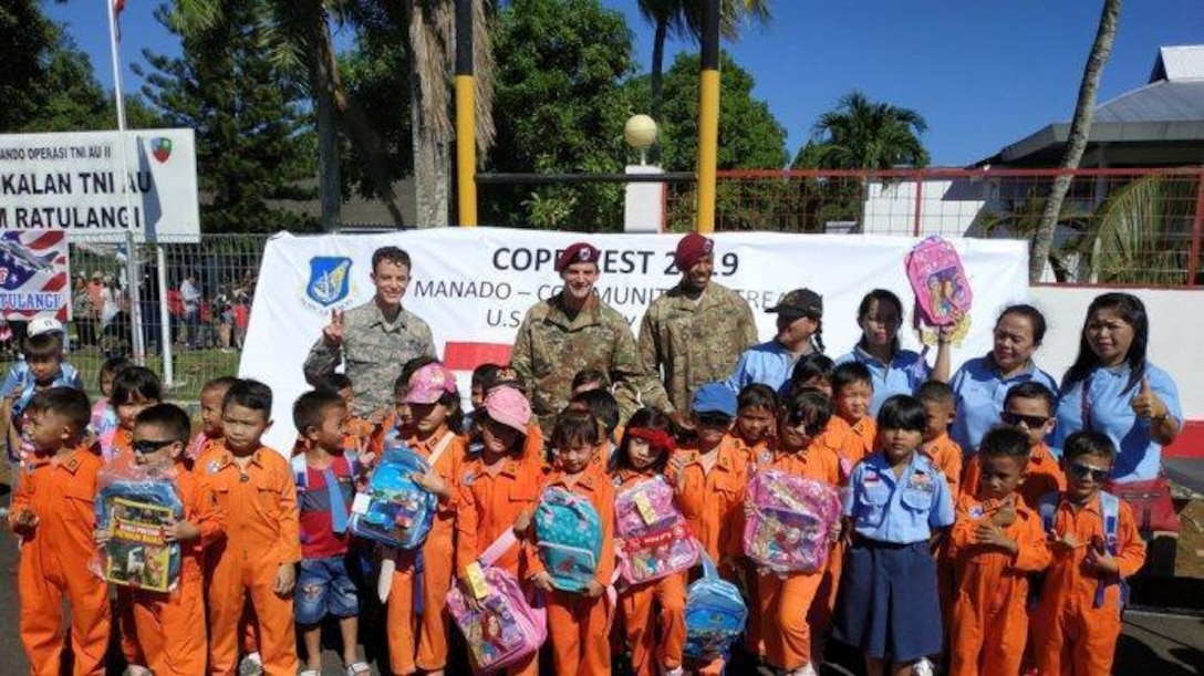 U.S. military members take a group photo with students from a local school during the Cope West 19 open house at Sam Ratulangi International Airport, Manado, Indonesia June 22, 2019.  During the event, a U.S. Indo-Pacific Command Team of U.S. Embassy-Jakarta members set up a small kiosk showcasing U.S.-Indonesian 70th anniversary bilateral relations items and educational handouts for children. The team handed out educational books, back packs, writing supply materials, in commemoration of diplomatic relations between the U.S. and Government of Indonesia. (Courtesy photo)