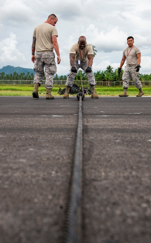 U.S. Air Force Tech. Sgt. DeMarco Poole, a 35th Civil Engineer Squadron electrical system craftsman from Misawa Air Base, Japan, spaces out the rollers on the mobile aircraft arresting system (MAAS) cable at the Sam Ratulangi International Airport, Manado, Indonesia, June 17, 2019. The small rollers keep the cable up off the runway so the hook can grab it. Six MAAS technicians forward deployed to Indonesia to support Cope West 19.The MAAS is designed to ensure pilots land and take-off safely in the event of an in-flight emergency. (U.S. Air Force photo by Staff Sgt. Melanie A. Hutto)