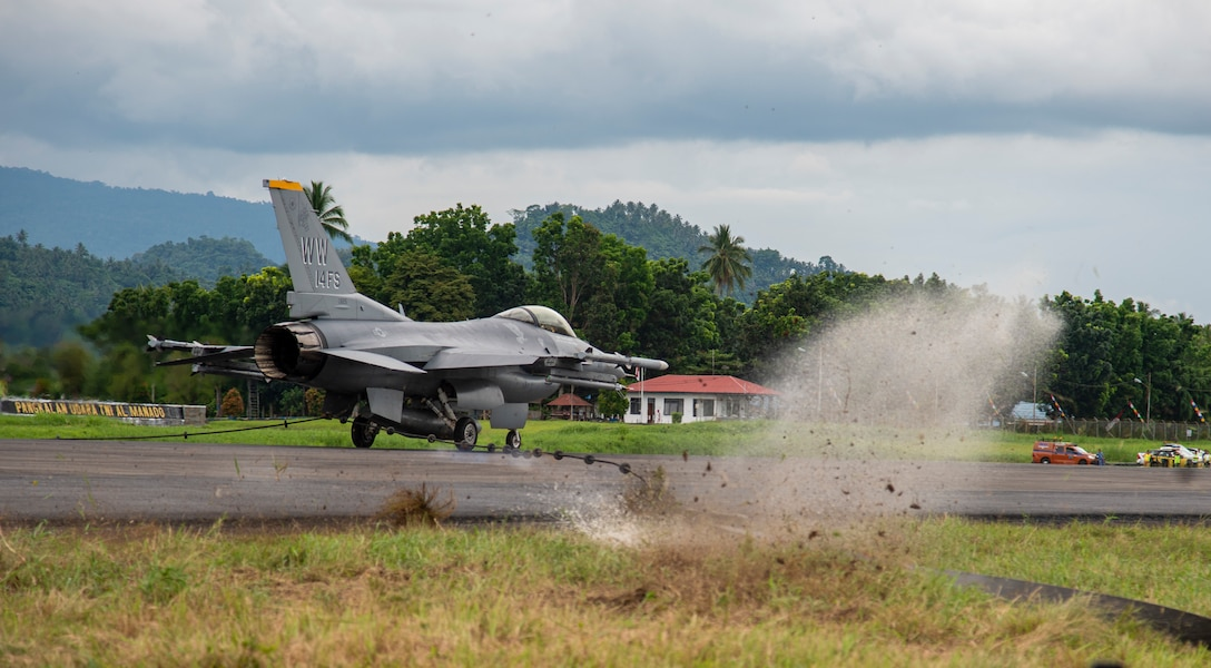 A U.S. Air Force F-16 Fighting Falcon from the 14 Fighter Squadron, Misawa Air Base, Japan,  pulls the mobile aircraft arresting system (MAAS) cable at the Sam Ratulangi International Airport, Manado, Indonesia, June 17, 2019. The MAAS is a contingency airfield asset that allows for the safe retrieval of tail hook aircraft during an in-flight emergency. It is air-portable and can be installed in a variety of methods and on practically any surface type to provide coverage in a variety of scenarios. (U.S. Air Force photo by Staff Sgt. Melanie A. Hutto)