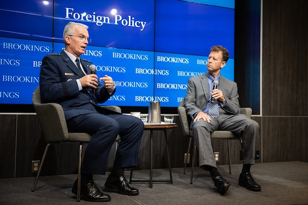 Two men talk, seated on stage with Brookings Institution backdrop.