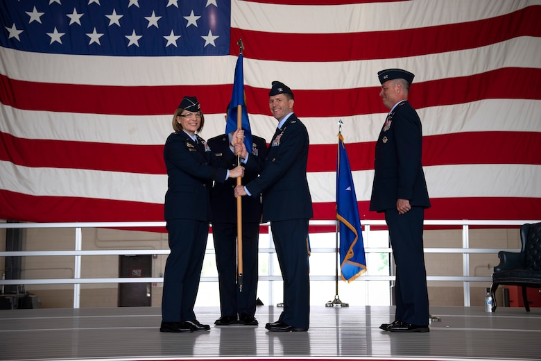 Col. Cameron Pringle, 319th Air Base Wing commander, assumes command in recieving the 319 ABW guidon from Maj. Gen. Mary O'Brian, 25th Air Force commander, during a change of command ceremony for the wing June 28, 2019, on Grand Forks Air Force Base, North Dakota.
