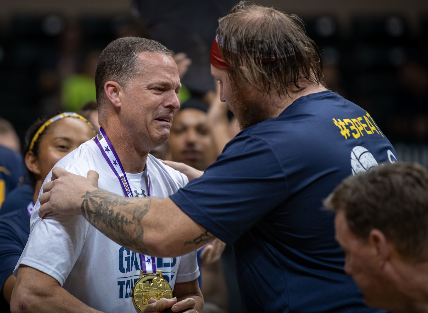 Navy Petty Officer 1st Class Tyson Schmidt, right, gives Navy Capt. Daryl Schaffer, left, his gold medal for sitting volleyball during the 2019 DoD Warrior Games at Yuengling Center in Tampa, Florida