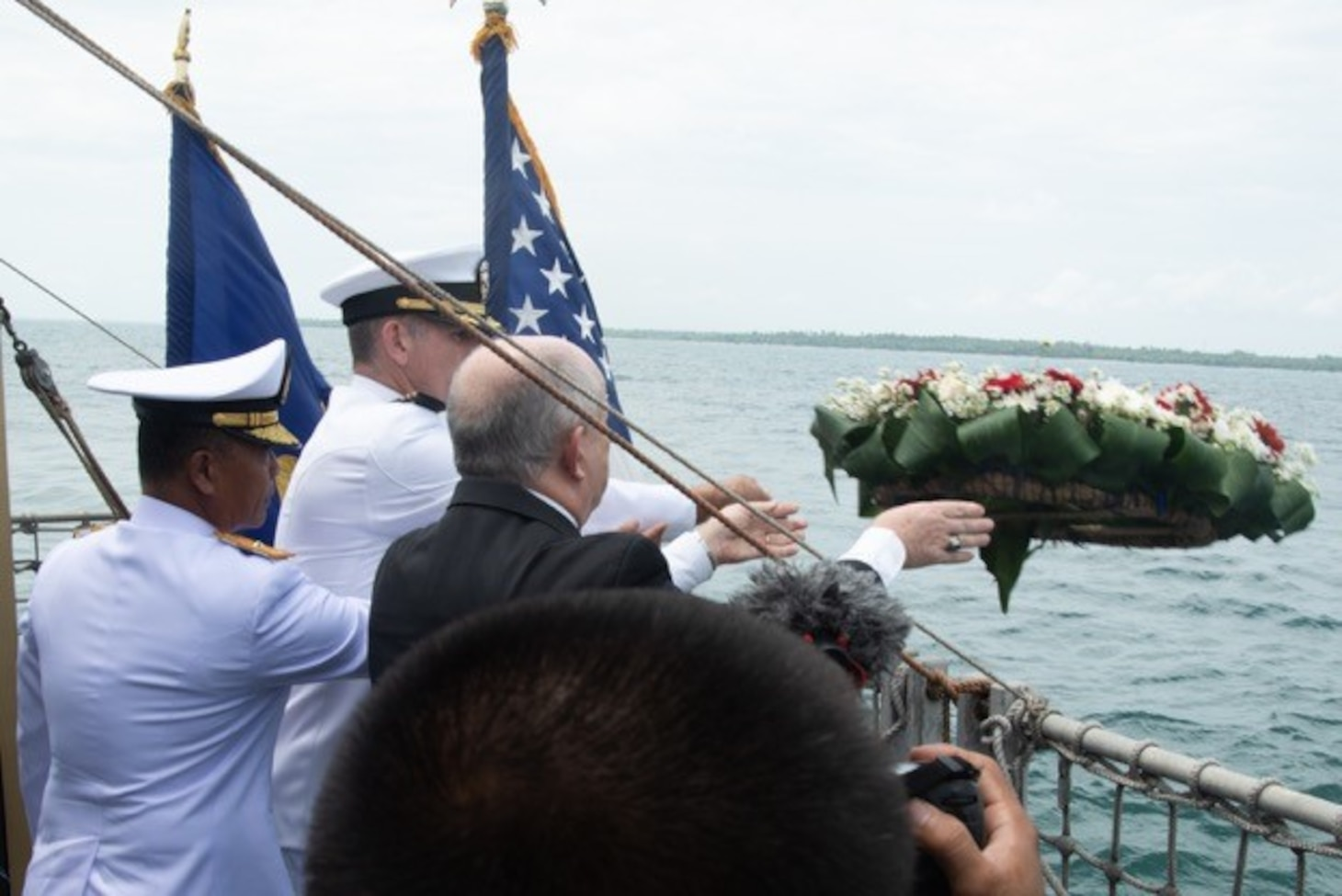 SUNDA STRAIT (March 1, 2019) U.S. Ambassador to Indonesia Joseph Donovan Jr. (right), Cmdr. Greg Adams (center), Naval Atache of U.S. Embassy Jakarta, and a senior leader of the Indonesian Navy (TNI-AL) lay a wreath during a memorial service aboard the Indonesian Navy ship Kri Usman Harun (359). The ceremony was held to honor the American and Australian crews of USS Houston (CA 30) and HMAS Perth (D 29) that lost their lives in battle against the Japanese Imperial Navy during World War II.