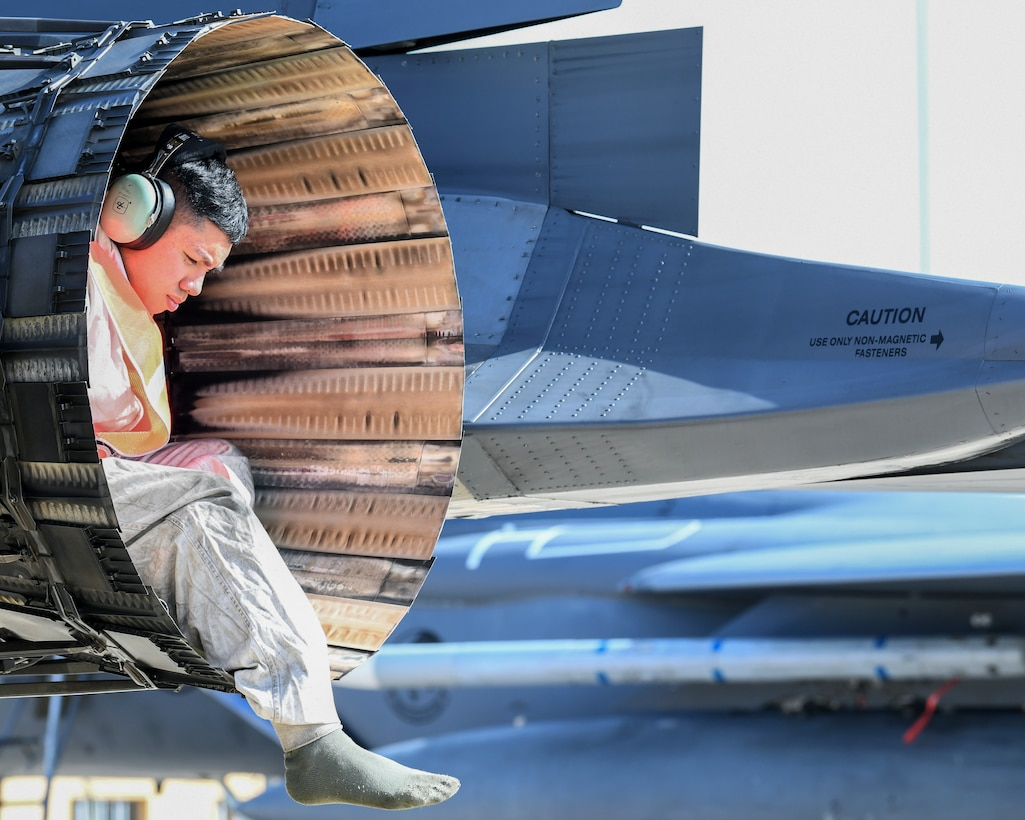An engine of an F-15E Strike Eagle with an Airman seated inside