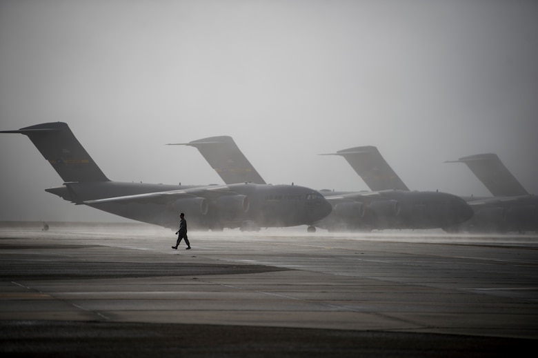 An Airmen walks past multiple C-17