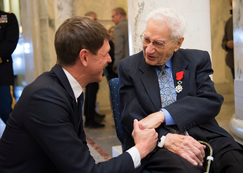 A World War II veteran and Purple Heart recipient, shakes the hand of French Consul