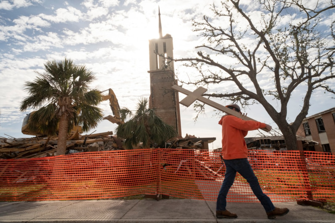 Kylan Nathey, a field operations manager, carries a cross from Chapel 2 at Tyndall Air Force Base, Fla., Feb. 15, 2019. The chapel was severely damaged by Hurricane Michael, a category 4 storm that made landfall on Oct. 10, 2018. The demolition marked the beginning of a long process to clear out damaged structures to make way for new construction. (U.S. Air Force photo by Senior Airman Javier Alvarez)