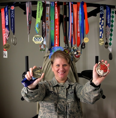 "Master Sgt. Cynthia Umscheid, 932nd Medical Group, shows off her two favorite marathon medals.  She was motivated to run more often and for longer distances by a disappointment.  ""Several years ago, I failed my Air Force fitness test; I was in school and not eating correctly.  I decided I needed a new goal to keep me going.  I thought about it and I wanted to do a run in every state in America, and sat down and made a long range plan,"" said Sergeant Umscheid.  