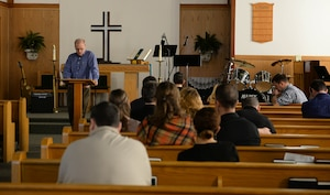 Chaplain (Col.) Doug Slater, Air Education and Training Command chaplain, from Joint Base San Antonio-Randolph, Texas, reads a section of the bible to attendees during service at the BLAZE Chapel Feb. 24, 2019, on Columbus Air Force Base, Mississippi. During the sermon, Chaplain Slater spoke to the audience about God's love and reminisced about his time as a teenager learning about God and how one small event initiated a chain reaction that led him to become who he is today. (U.S. Air Force photo by Airman Hannah Bean)