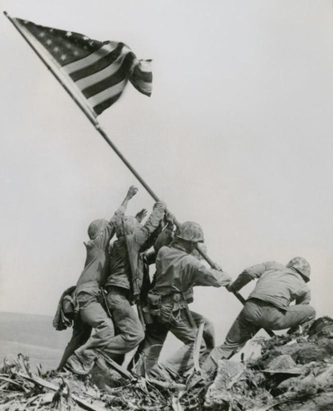 Marines in uniform raise the American flag.