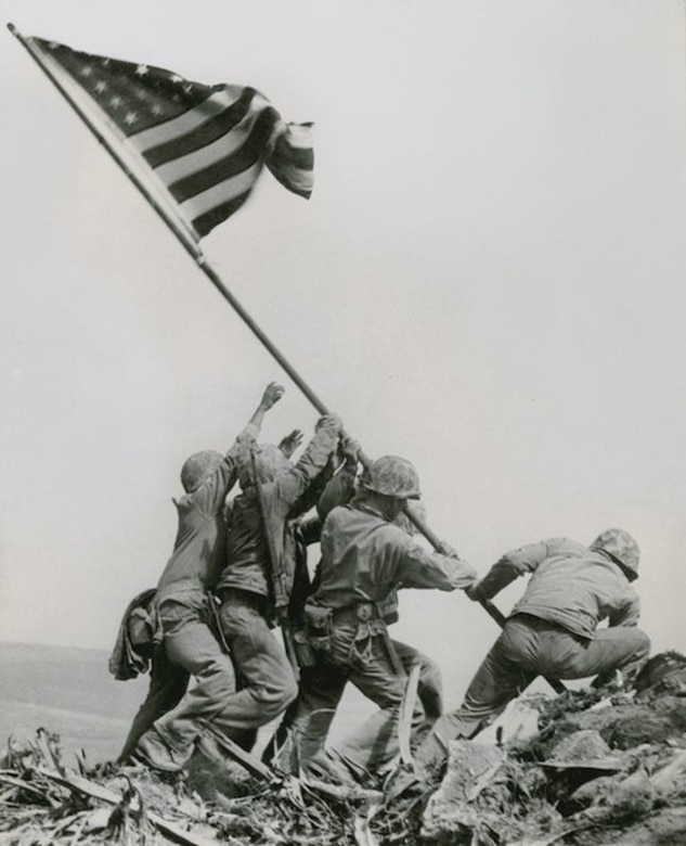 Marines in uniform raise the American flag.