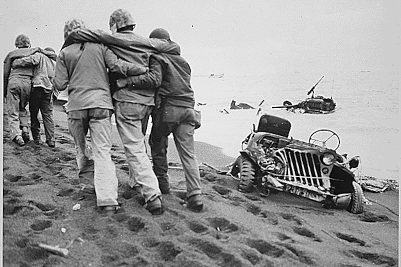 Men walk on a beach as a destroy Jeep sinks into sand.