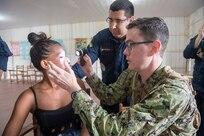 Lt. Cmdr. John Roman and Brazilian navy 1st Lt. Gilvan Martins examine a patient during a medical clinic in Vencedor, Brazil, Feb. 27.