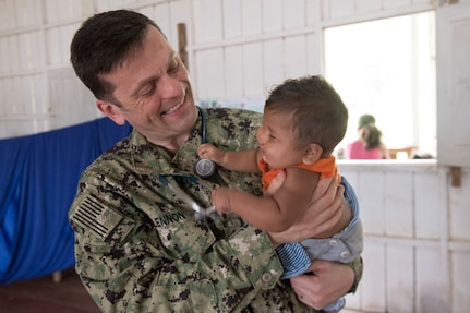 Lt. Cmdr. Robert Lennon meets with a young patient during a medical clinic in Vencedor, Brazil, Feb. 27.