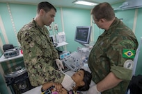 Lt. John Sullivan conducts thyroid ultrasound training with Brazilian navy Cmdr. Carlos Marsico aboard Brazilian navy hospital ship NAsH Carlos Chagas (U 19) off the coast of Prainha, Brazil during a medical clinic, Feb. 26.