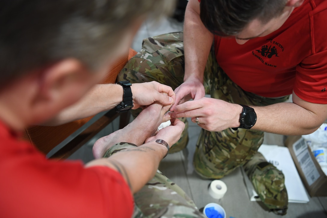 A Special Operations Surgical Team member with the 24th Special Operations Wing bandages a Special Tactics Airman's foot during the Special Tactics Memorial March, Feb. 27, 2019, in Louisiana. Twenty Special Tactics Airmen ruck from the Medina Annex at Joint Base San Antonio-Lackland, Texas, to Hurlburt Field, Fla., to pay tribute to Staff Sgt. Dylan J. Elchin, who was killed in Afghanistan, Nov. 27, 2018, and 19 other Special Tactics Airmen who have been killed in action since 9/11. The ruck march takes Special Tactics members across five states and 830 miles. (U.S. Air Force photo by Senior Airman Ridge Shan)