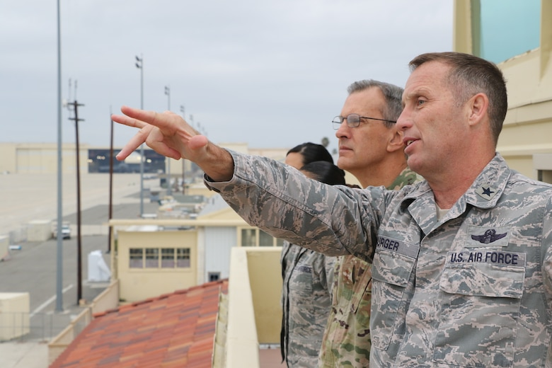 U.S. Air Force Brig. Gen. Matthew Burger, commander, 452nd Air Mobility Wing, March Air Reserve Base, points toward multiple C-17 Globemaster III aircraft on the flight line here as U.S. Air Force Maj. Gen. Randall Ogden, commander, Fourth Air Force, March ARB observes Feb. 9, 2019