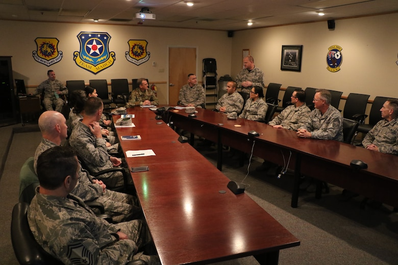 U.S. Air Force Maj. Gen. Randall Ogden (center), commander, Fourth Air Force, March Air Reserve Base, listens to a mission briefing here by U.S. Air Force Col. Aaron Heick (right standing), commander, 452nd Maintenance Group, March ARB, Feb 10, 2019. 4AF senior leadership toured March ARB to learn about the 452nd AMW's mission, capabilities and challenges as part of a multi-day unit visit.