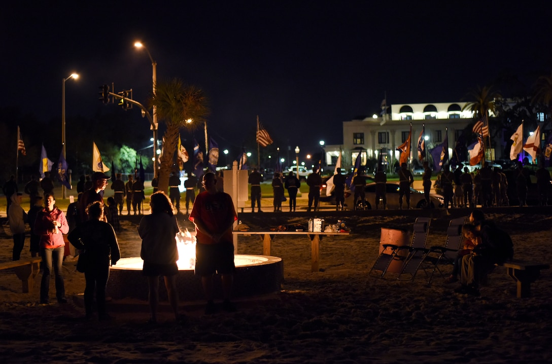 Airmen and volunteers light fires and line the a street with flags in a show of support for a team of Special Tactics Airmen ruck marching through Biloxi, Mississippi March 1, 2019. Twenty Special Tactics Airmen ruck from Medina Annex at Lackland Air Force Base, Texas, to Hurlburt Field, Florida, to pay tribute to Staff Sgt. Dylan J. Elchin, who was killed in Afghanistan on Nov. 27, 2018, and 19 other Special Tactics Airmen who have been killed in action since 9/11. More than 40 Airmen from Keesler joined the team for the portion of the march that passed through Biloxi. The ruck march takes ST members across five states and 830 miles. (U.S. Air Force photo by Master Sgt. Ryan Crane)