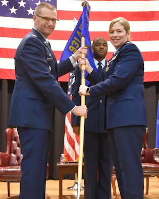 (Left to right) Col. Phil Heseltine, 931st Air Refueling Wing commander, takes the guidon from Maj. Amy White, outgoing 931st Force Support Squadron commander, during an official change of command ceremony March 2, 2019, McConnell Air Force Base, Kan.  White has commanded the 931 FSS since 2015.