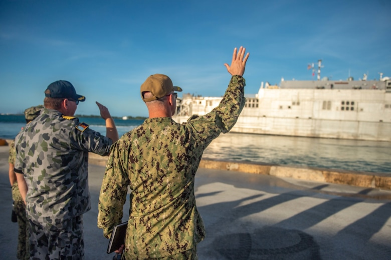 SANTA RITA, Guam (March 4, 2019) Royal Australian Navy Capt. Brendon Zilko, left, and Pacific Partnership 2019 Mission Commander U.S. Navy Capt. Randy Van Rossum wave to the Military Sealift Command expeditionary fast transport ship USNS Brunswick (T-EPF 6) as it departs Naval Base Guam for Pacific Partnership 2019. Pacific partnership, now in its 14th iteration, is the largest annual multinational humanitarian assistance and disaster relief preparedness mission conducted in the Indo-Pacific. Each year, the mission team works collectively with host and partner nations to enhance regional interoperability and disaster response capabilities, increase security and stability in the region, and foster new and enduring friendships in the Indo-Pacific.