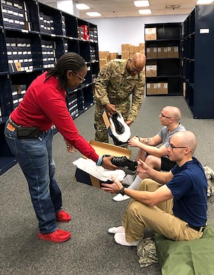 Vernalynne Carter, chief of clothing initial issue for the Air Force, and 502nd Logistics Readiness Squadron Commander Air Force Lt. Col. Ernest Cage issue new American-made athletic footwear to recruits Daniel Sterling (bottom right) and Ryan Padro (top right) at Joint Base San Antonio-Lackland, Texas, in January.