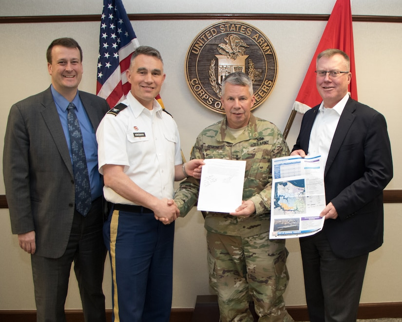 Greg Steele, left, Norfolk District Water Resources Division chief, along with Mike Darrow, right, Norfolk District deputy district engineer for project management, and Col. Patrick Kinsman, Norfolk District commander, hold up the signed Chief's Report for the Norfolk Coastal Storm Risk Management with Lt. Gen. Todd T. Semonite, USACE commanding general.