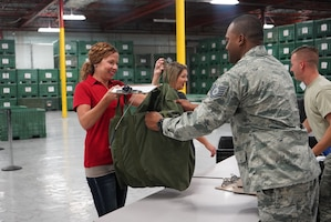 Spouses are given mobility bags to simulate what a deployment line at MacDill Air Force Base, Fla., on March 2, 2019. The Spouses were given the bags before they took flight to get a firsthand look at the mission. (U.S. Air Force photo by Senior Airman Alexis Suarez)
