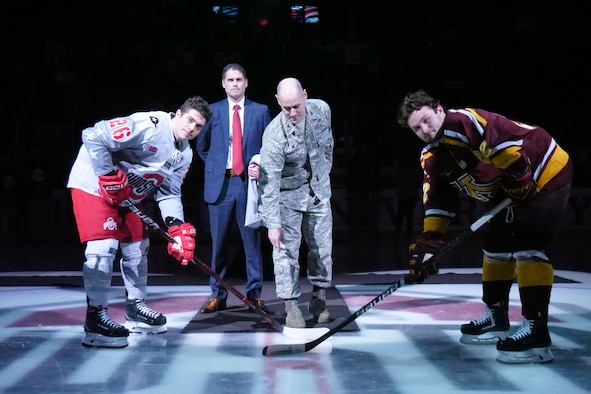 Col. Michael Foutch, 88th Medical Group commander, drops the ceremonial first puck at the Military Appreciation game between the Ohio State Buckeyes and the Minnesota Golden Gophers at the Value City Arena Schottenstein Center in Columbus, Ohio Feb. 15, 2019.