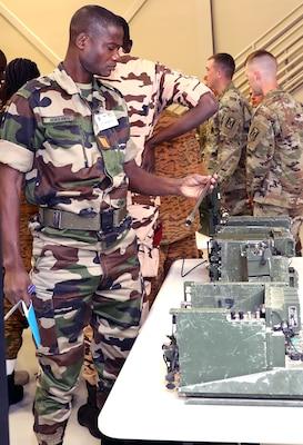 Sgt. Katakoa Momoga, Togo communications non-commissioned officer, inspects radio equipment during the 2019 Junior Communications Symposium at Joint Base San Antonio-Fort Sam Houston Feb. 25. Momoga is one of 18 communicators who participated in the symposium.