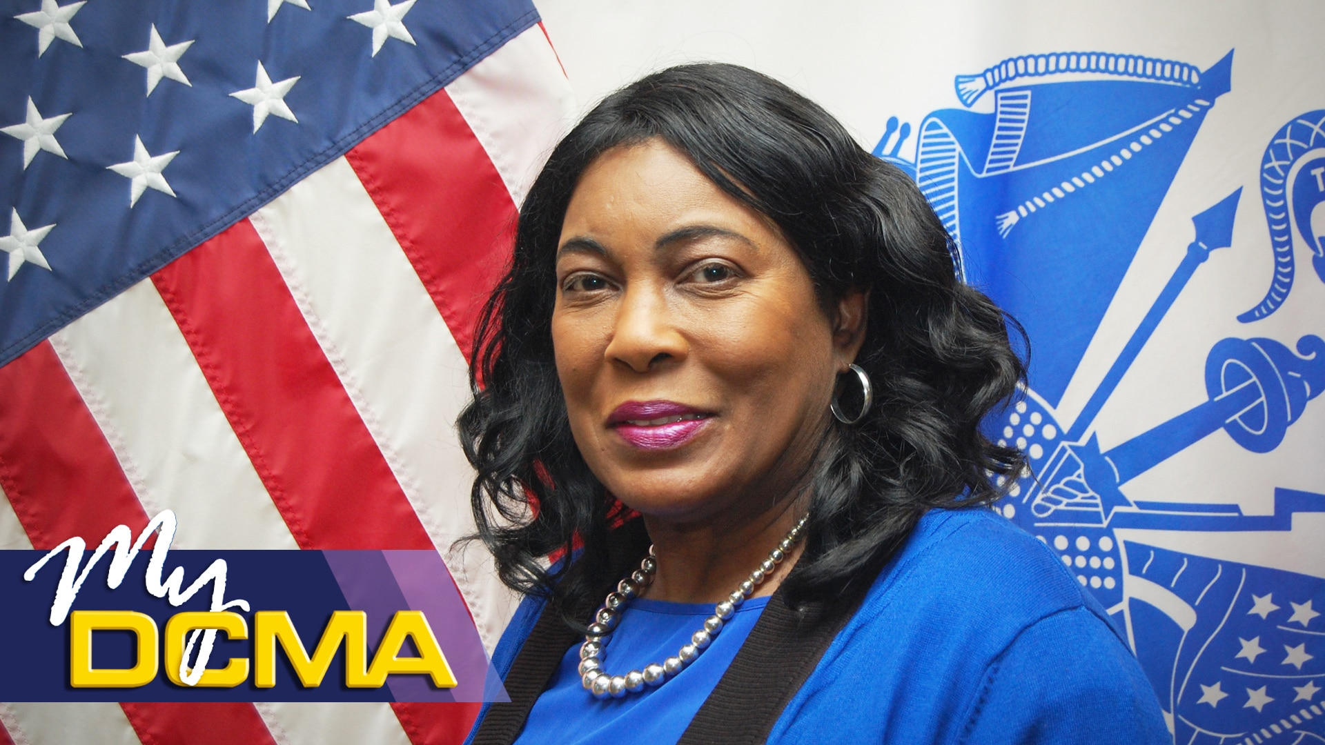Picture of a smiling lady wearing a blue blouse standing in front of the American flag
