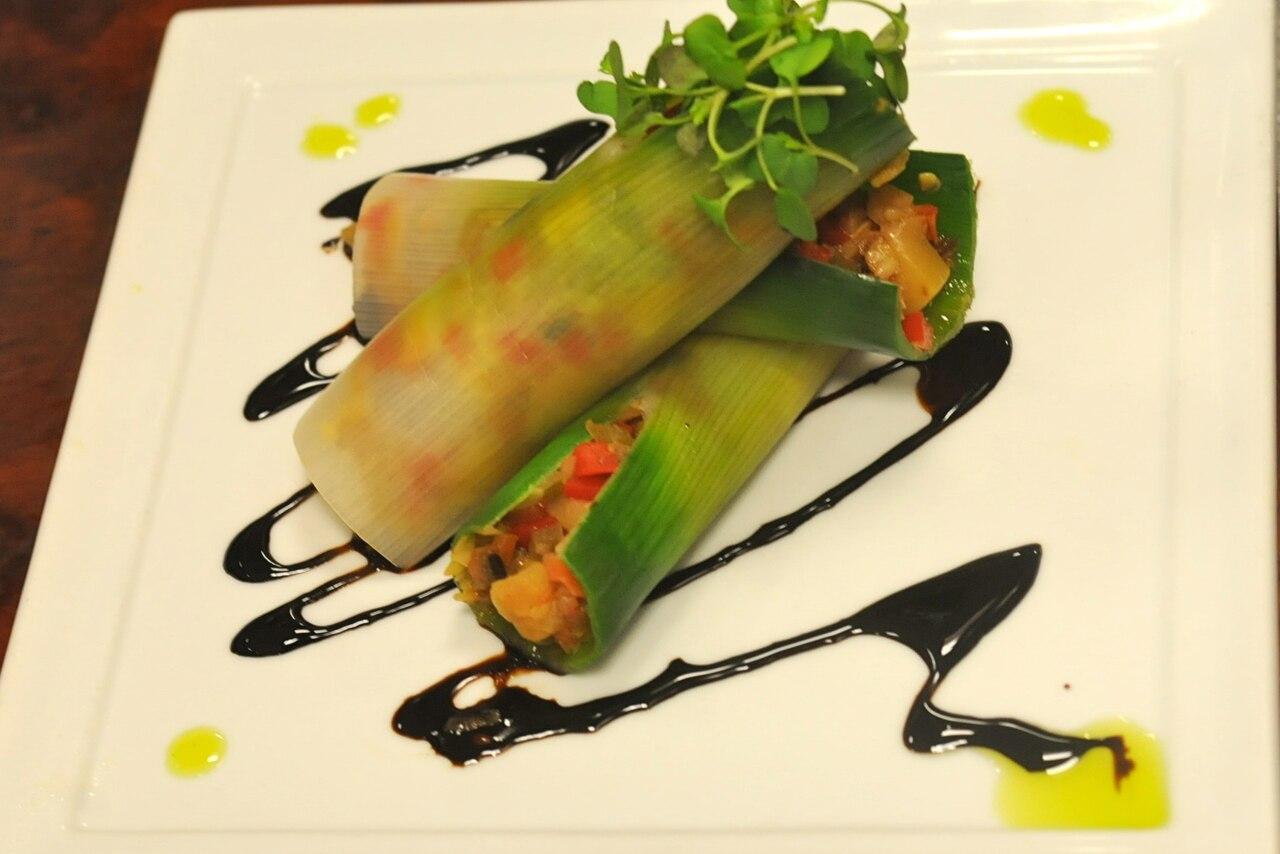 Ratatouille -stuffed leeks are displayed on a white plate.
