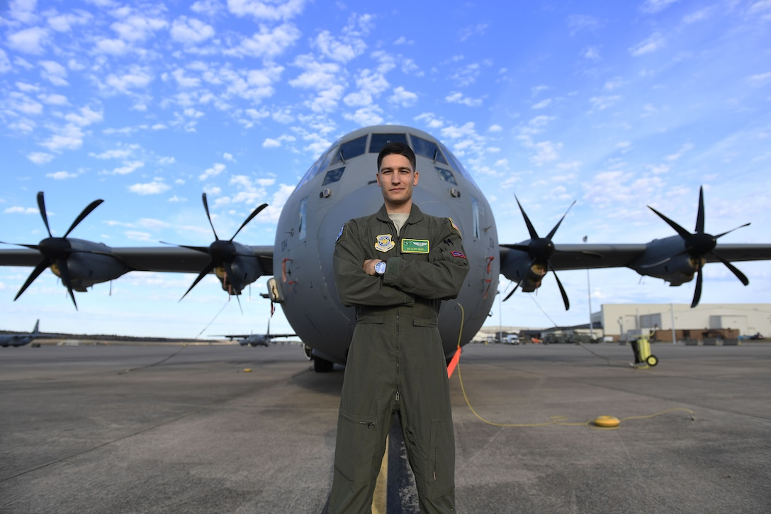 Airman stands with arms crossed in front of C-130J.