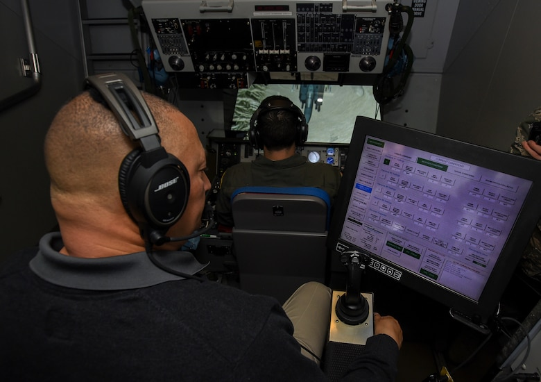 Steven Custis, KC-10 Extender boom operator instructor, oversees Airman 1st Class Nicholas Eddings, 32nd Air Refueling Squadron KC-10 boom operator, during a simulated refueling mission on Joint Base McGuire-Dix-Lakehurst, New Jersey, Dec. 19, 2018. Crewmembers train in simulators that include a hydraulics system that mimics the sensation of an aircraft. (U.S. Air Force photo by Airman 1st Class Ariel Owings)