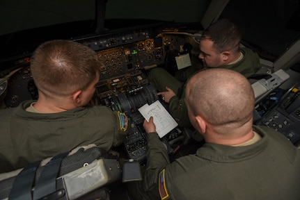 U.S. Air Force 2nd Lt. Kyle Mallard, 78th Air Refueling Squadron KC-10 Extender pilot trainee, Tech. Sgt. Jon Lynes, 32nd Air Refueling Squadron KC-10 flight engineer, and U.S. Air Force Capt. Zachary White, 2nd Air Refueling Squadron KC-10 pilot, read checklists during their initial qualification on a simulator on Joint Base McGuire-Dix-Lakehurst, New Jersey, Dec. 19, 2018. Students must pass their initial qualification tests in the simulator before they operate in a KC-10. (U.S. Air Force photo by Airman 1st Class Ariel Owings)