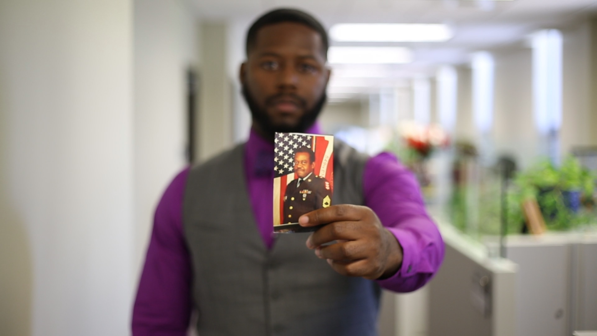 Man holds photo of another man in military uniform towards camera.
