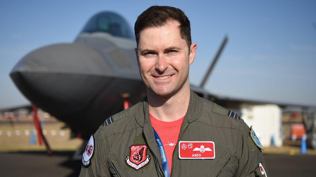 Royal Australian Air Force Flight Lt. Paul Anderton, an F-22 Raptor pilot with the 90th Fighter Squadron, Joint Base Elmendorf-Richardson, Alaska, stands in front of a Raptor at Geelong, Victoria, Australia, Feb. 28, 2019.