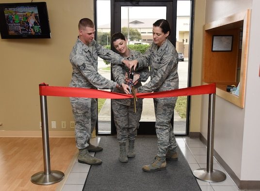 "U.S. Air Force Staff Sgt. Aron Alt, 81st Force Support Squadron fitness assessment cell NCO in charge, Maj. Amber Ortiz, 81st FSS commander, and Col. Marcia Quigley, 81st Mission Support Group commander, officially open the new Fitness Assessment Cell during a ribbon cutting ceremony at Keesler Air Force Base, Mississippi, March 1, 2019. The FAC moved to a new location, building 4104, near the Dragon Fitness Center, to better suit Keesler's fitness needs by enhancing the options for members when choosing where they're most comfortable accomplishing the aerobic component of the test. Airmen are now able to choose between using either the Crotwell Track or the Triangle Track. ""The greatest benefit is that we are providing a location that is fit for the mission,"" said Ortiz. (U.S. Air Force photo by Kemberly Groue)"