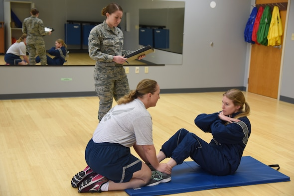 U.S. Air Force Airman 1st Class Alexus Barrington, 81st Inpatient Operation Squadron aerospace medical technician and physical training leader, counts the number of push-ups that Senior Airman Rebecca Fentress, 81st Security Forces Squadron investigator, completes as Senior Master Sgt. Rebecca Janssen, 85th Engineering Installation Squadron operations flight chief, holds her feet inside the new fitness assessment cell building at Keesler Air Force Base, Mississippi, March 4, 2019. The FAC moved to a new location, building 4104, near the Dragon Fitness Center, to better suit Keesler's fitness needs by enhancing the options for members when choosing where they're most comfortable accomplishing the aerobic component of the test. Airmen are now able to choose between using either the Crotwell Track or the Triangle Track. Staff Sgt. Aron Alt, 81st Force Support Squadron fitness assessment cell NCO in charge, said he thinks the customer service environment as a whole will be better and that when you show Airmen you care about them they tend to give a better over all performance. (U.S. Air Force photo by Kemberly Groue)
