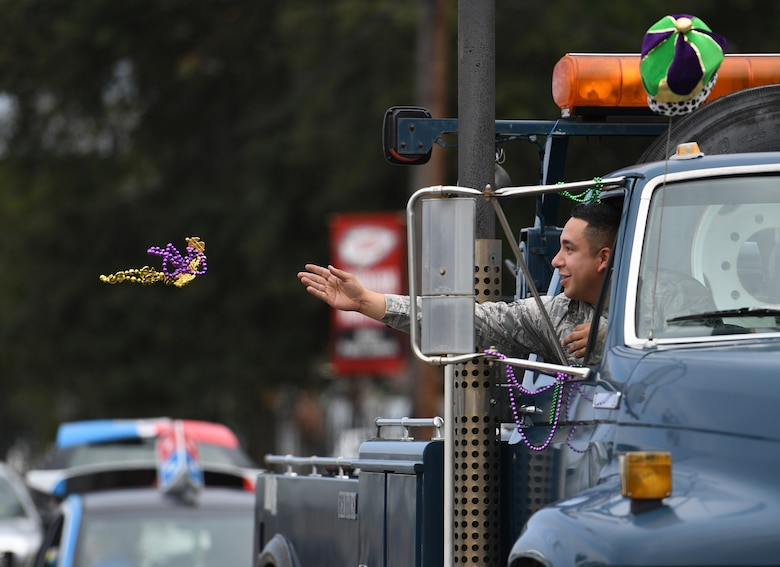 U.S. Air Force Senior Airman Andrew Hernandez, 81st Logistics Readiness Squadron training and validation, tosses beads to children during the Jeff Davis Elementary School Mardi Gras parade in Biloxi, Mississippi, March 1, 2019. Keesler leadership, Honor Guard and Airmen participated in various festivities throughout the Mardi Gras season, which is celebrated by the local communities. (U.S. Air Force photo by Kemberly Groue)