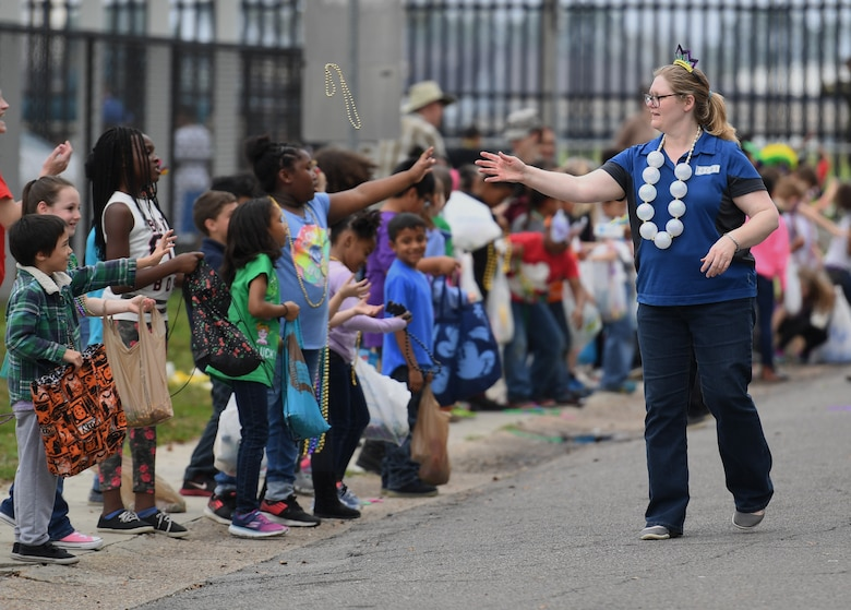 Diane Cook, Families Overcoming Under Stress (FOCUS) resilience trainer, tosses beads to children during the Jeff Davis Elementary School Mardi Gras parade in Biloxi, Mississippi, March 1, 2019. Keesler leadership, Honor Guard and Airmen participated in various festivities throughout the Mardi Gras season, which is celebrated by the local communities. (U.S. Air Force photo by Kemberly Groue)